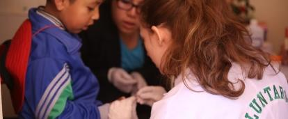 A high school student takes a child's blood sugar measure on our medical internship in Peru
